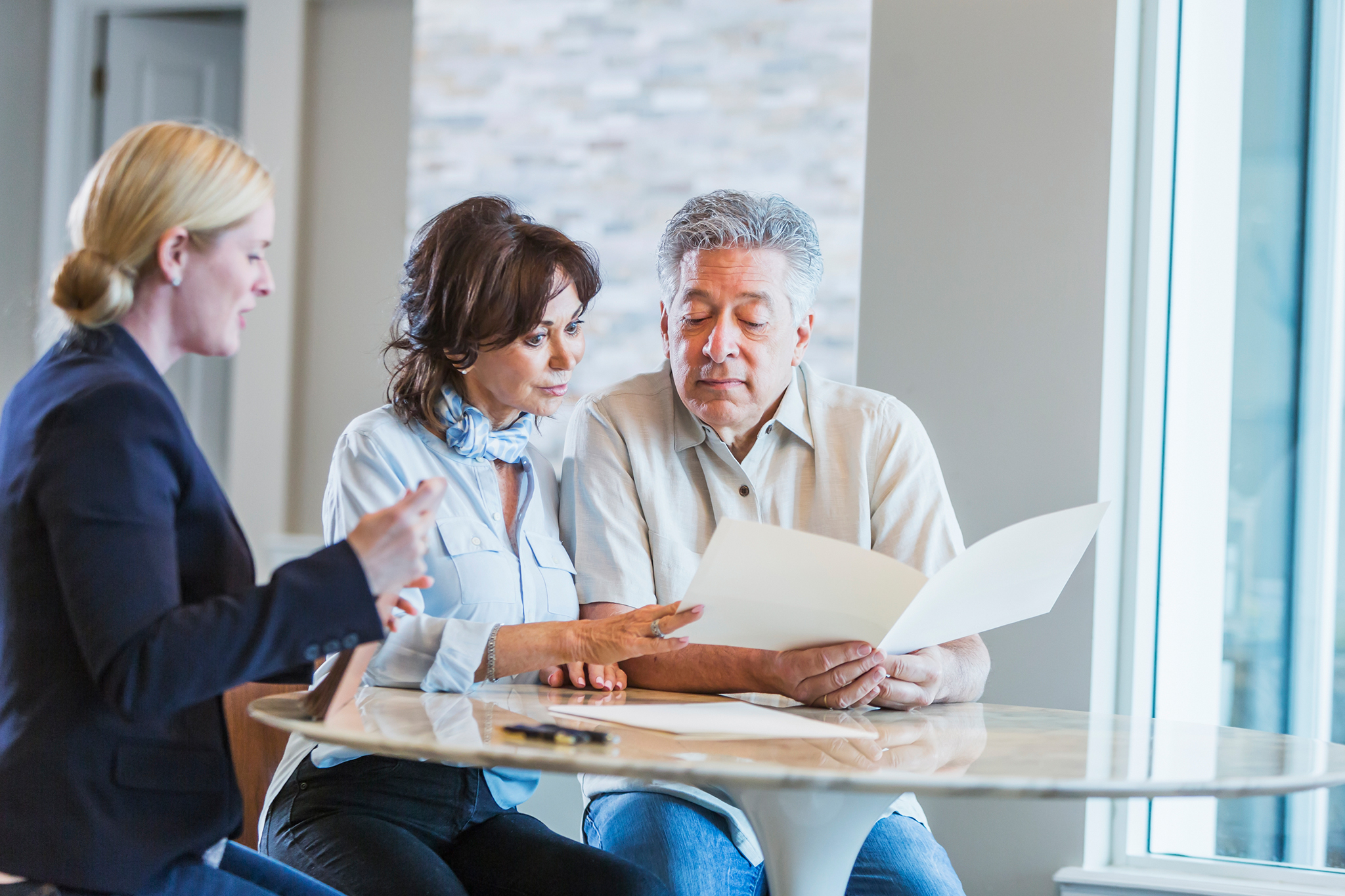 Middle-aged couple going over their life settlement with a financial professional